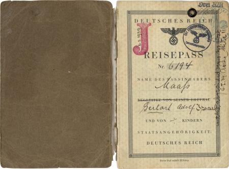 """Deux pages d'un passeport. Sur la première page du passeport, un """"J"""" rouge est estampé sur la droite et la date 1/1/1939 est indiquée à l'aide d'une étampe circulaire à l'encre du président de la police de Hambourg, et il y a une autre étampe circulaire à l'encre verte. Il y a de l'écriture manuscrite le long des bordures de la page."""