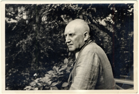 Photo en noir et blanc d'un homme âgé posant de profil à l'extérieur, entouré de feuilles et de feuillage. Il regarde au loin.
