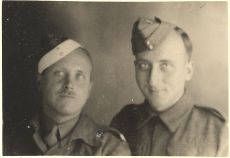 Black-and-white photograph of two men dressed in military uniform, smiling at the camera. The man on the left has a moustache.