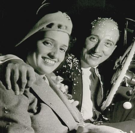 Photo en noir et blanc de forme carrée d'un homme et d'une femme assis ensemble dans une voiture, souriant. L'homme est couvert de confettis et entoure la femme de son bras.