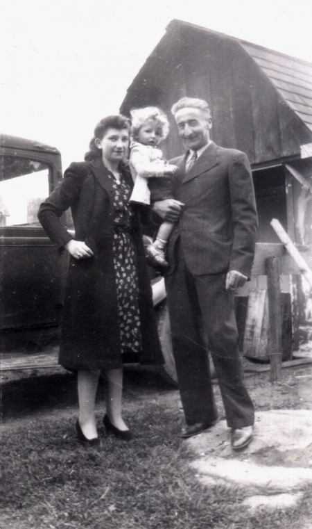 Black-and-white photograph of a man and woman with a young child with curly blond hair. They stand together outdoors in front of a truck and a barn in the background.