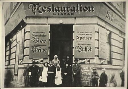 Photo en noir et blanc d'un groupe d'environ huit personnes se tenant devant l'entrée d'un restaurant. L'édifice a une grande affiche de chaque côté de la porte, rédigées en allemand. Deux jeunes enfants regardent le groupe d'un des deux côtés.