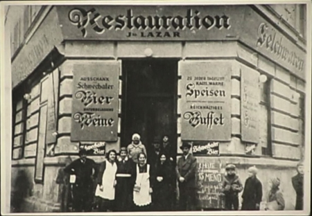 Black-and-white grainy photograph of a group of about 8 people standing in front of the entrance to a restaurant. The building has large signs on either side of the door, written in German. A couple young children look at the group from the side.