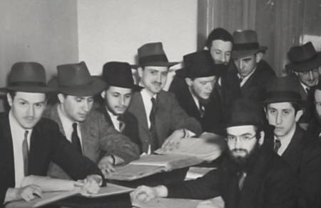 Photo en noir et blanc d'un groupe de dix hommes assis ensemble à une table couverte de livres et de papiers. Les hommes portent des costumes et des chapeaux.