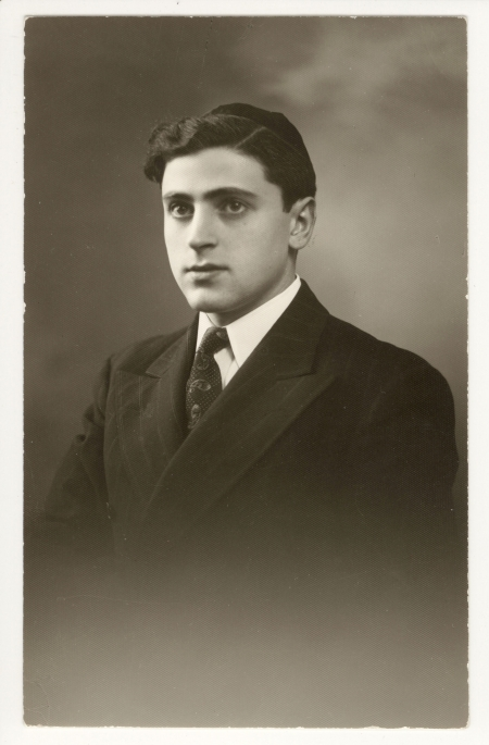 Black-and-white portrait photograph of a man in a suit and tie, looking towards the left of the camera. He wears a kippah on his head.