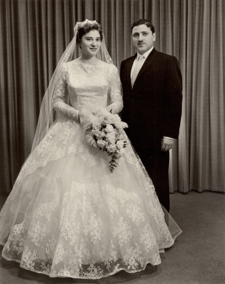 Photo en noir et blanc d'un homme et d'une femme le jour de leur mariage. La femme porte une longue robe blanche et un voile et tient un bouquet de fleurs, et l'homme porte un costume formel ainsi qu'une moustache.