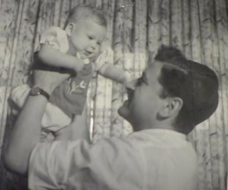Photo en noir et blanc d'un homme de profil tenant un bébé dans les airs et regardant le bébé dans ses bras. Le bébé le regarde et a les bras tendus vers lui et sourit à l'homme.