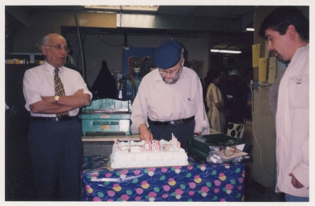 Colour photograph of an elderly man with a beard and cap, cutting into a large cake while two men stand on either side watching him.
