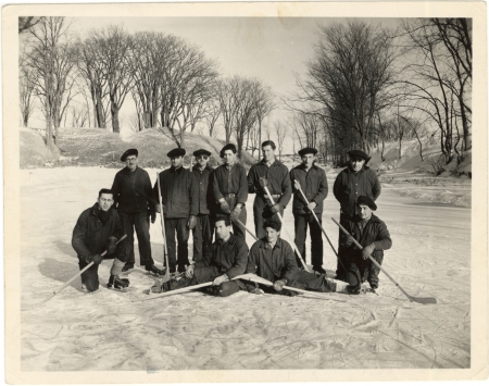Black-and-white photograph of a hockey team of 11 men, posing together with hockey sticks on an ice rink outdoors. Trees are visible in the background.