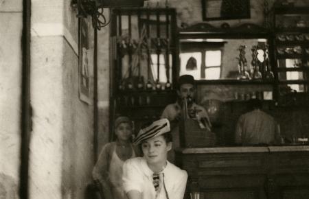 Photo en noir et blanc d'une femme assise à un café, portant une blouse blanche et un béret. La femme regarde de côté. un jeune garçon et deux hommes sont debout derrière le bar en arrière-plan.