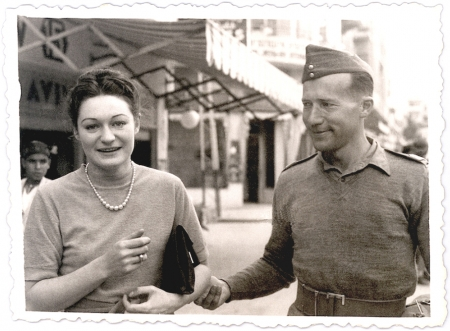 Black-and-white photograph of a woman and man outdoors. The woman holds a clutch purse under her arm and faces the camera, smiling. The man looks at the woman and holds her elbow.