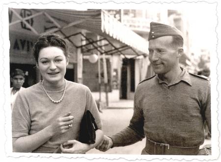 Photo en noir et blanc d'une femme et d'un homme à l'extérieur. La femme tient une petite bourse sous son bras et fait face à la caméra en souriant. L'homme regarde la femme et lui tient le coude.