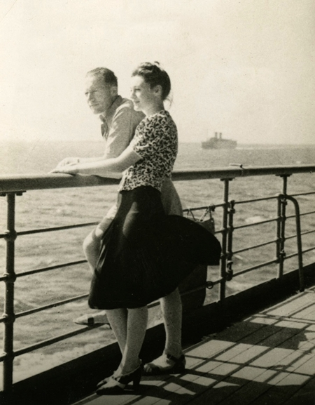Black-and-white photograph of a woman standing beside a man on the deck of a ship. They both look ahead of them, leaning on the railing of the deck. There is water below them and a ship on the far horizon.