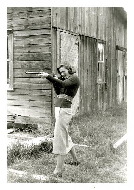 Photo en noir et blanc d'un femme debout devant une grange. Elle tient un fusil et le pointe à gauche de la caméra.