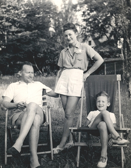 Black-and-white photograph of a woman standing between a man and young boy, who are both sitting with their legs crossed in lawn chairs outside in a field. All three individuals are dressed in shorts and summer clothing.