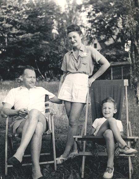 Photo en noir et blanc d'une femme debout entre un homme et un jeune garçon, qui sont tous deux assis les jambes croisées sur des chaises de jardin. Ils portent tous les trois des shorts et des vêtements estivaux.