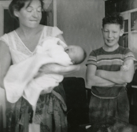 Black-and-white photograph of a young boy standing with his arms crossed and smiling beside a woman who holds a crying baby wrapped in a blanket.