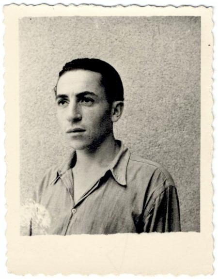 Photo en noir et blanc de forme carrée avec une bordure de polaroid d'un jeune homme regardant vers la gauche de la caméra. Ses cheveux sont coiffés vers l'arrière et il porte une chemise à col.
