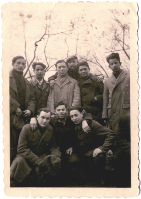 Black-and-white photograph of a group of 9 young men posing together arm-in-arm outdoors. They wear coats and there are bare trees above them in the background.