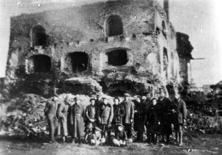 Black-and-white grainy photograph of a group of 15 people posing together outdoors in a line, 2 children sitting on the ground, in front of the ruins of a building. The building is missing a roof and has several window frames that no longer have any windows.