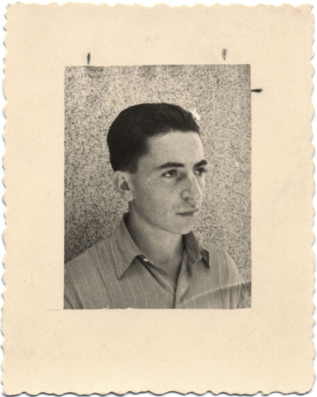 Photo en noir et blanc avec une grande bordure blanche d'un jeune homme regardant à droite de la caméra. Ses cheveux sont coiffés vers l'arrière et il porte une chemise à col.