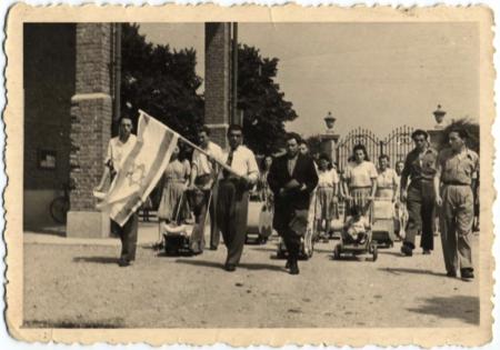 Photo en noir et blanc d'un défilé ou une marche avec un grand groupe de personnes marchant vers la caméra. Un homme à l'avant de la foule porte le drapeau d'Israël, et plusieurs femmes en arrière-plan poussent des poussettes.