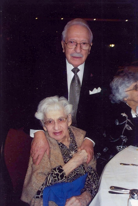Colour photograph of two elderly people smiling at the camera. The man stands behind the woman, who is sitting at a chair, with his hands on her shoulders. She holds one of his hands.