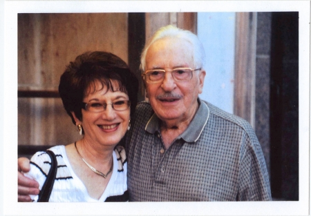 Colour photograph of an elderly couple smiling arm-in-arm at the camera. Both wear glasses, and the woman has dark brown short hair.