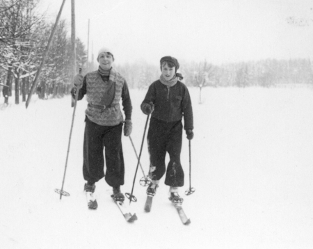 Photo en noir et blanc d'une femme et d'un jeune garçon portant des vêtements d'hiver et faisant du ski de fond sur un terrain enneigé.