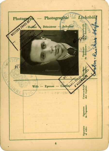 Beige-coloured page of an official document containing several stamps, signatures, and handwriting. One page includes a black-and-white portrait of a young man with combed-back hair and a suit and tie, positioned sideways on the top of the page.