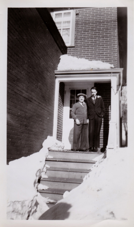 Black-and-white photograph of two men standing on the front porch of a brick house with snow in the foreground. Both men wear su