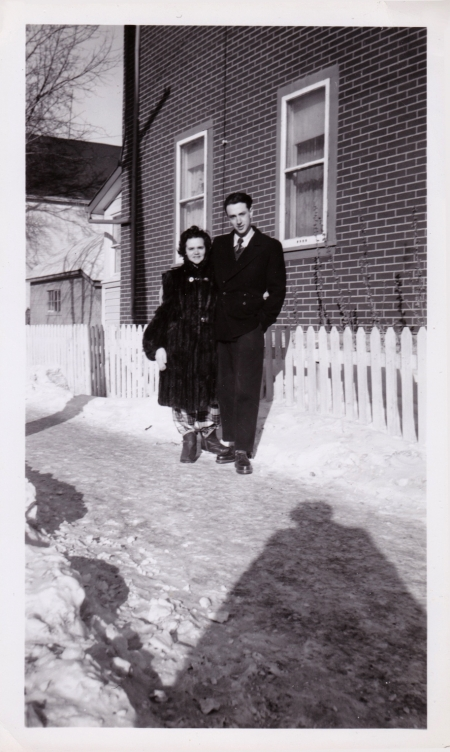 Black-and-white photograph of a woman and man standing together outdoors on a snowy driveway in front of a white fence. The woma