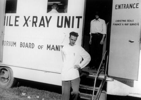 """Black-and-white photograph of a man, standing with a hand on his left hip, in front of a large white truck that reads """"X-RAY UNIT"""" on its side. A man stands behind him inside the entrance of the truck with his face covered by shadow."""