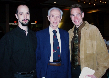 Colour photograph of three men, shown from the waist upwards, smiling at the camera. The elderly man in the middle wears a blue suit and tie, the man on the left wears a black shirt and has facial hair. The man on the right wears a camel jacket and brown shirt with tie.
