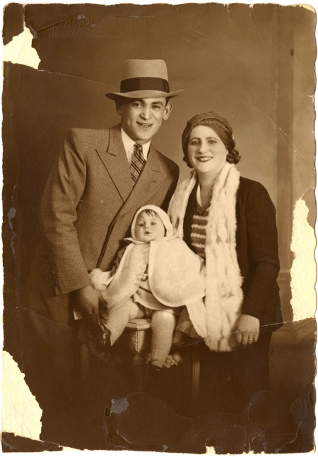 Photo de couleur sépia d'un homme et d'une femme prenant la pose avec un bébé pour un portrait. L'homme porte un chapeau ainsi que costume et cravate, et la femme porte aussi un chapeau. Le bébé porte une cape blanche. Les bords de la photo sont un peu usés et déchirés.