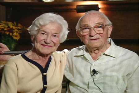 Colour photograph of an elderly couple sitting arm-in-arm and smiling at the camera. The woman on the left has short hair and wears a cardigan, and the man wears glasses and a collared shirt.