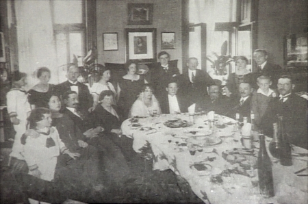 Black-and-white photograph of a group of about 20 people sitting and standing around a large dining table set with dishes. The group is formally dressed, and a couple sitting at the table appear to be celebrating their wedding.