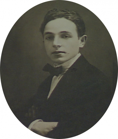 Black-and-white oval-shaped studio photograph of a young man. The man wears a suit with a bowtie. The photograph has a large white border.