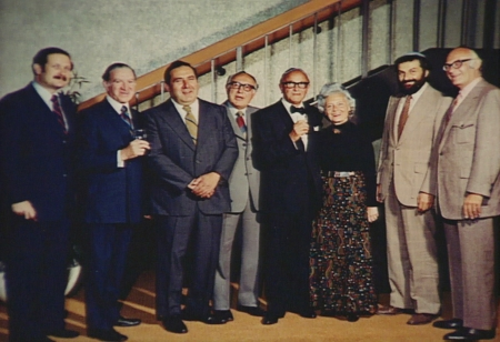 Colour photograph of a group of eight people standing together indoors in a line, smiling at the camera. The seven men wear suits, and the woman in the group wears a long dress.