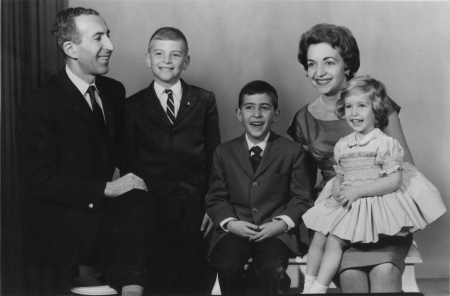 Photo en noir et blanc prise en studio d'un homme et d'une femme avec leur trois jeunes enfants, souriant à la caméra. L'homme et les deux garçons portent des complets, et la femme et sa fille portent des robes.