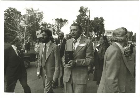Photo en noir et blanc de quatre hommes menant une marche à l'extérieur. L'homme au centre transporte une boîte de forme rectangulaire. Un groupe de personnes les suit en arrière-plan.