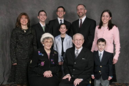 Colour studio photograph of nine people grouped together as a family in two rows, smiling at the camera.