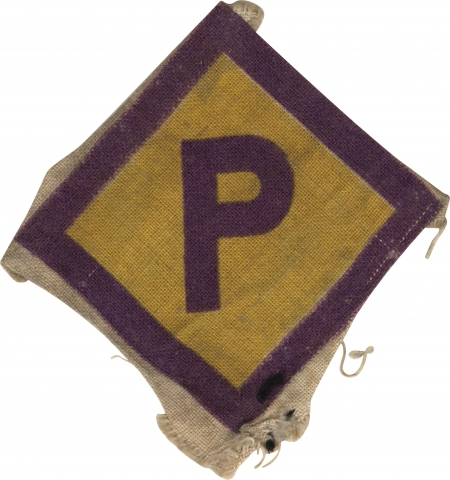 Colour photograph of a fabric badge in the shape of diamond. The centre is yellow with purple borders. In the middle of the badge is the capital letter 'P' in purple.
