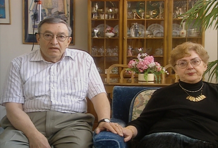Colour photograph of a elderly man and woman sitting together indoors, holding hands. The woman sits on a blue arm chair. There is a display cabinet containing dishes and chinaware in the background.