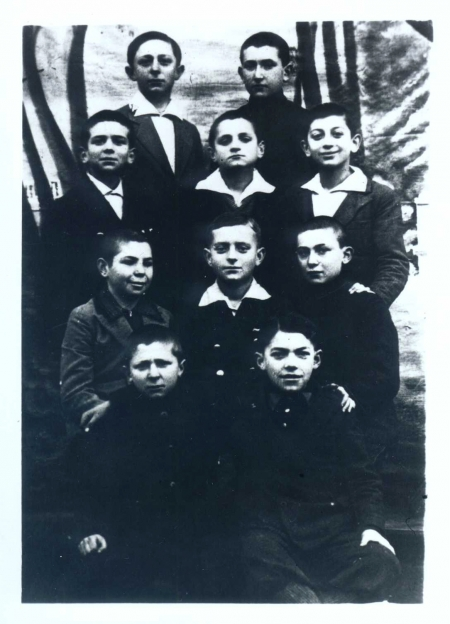 Black-and-white photograph of a group of ten young boys, posing in four rows of two or three. The boys look at the camera, most of them wearing collared shirts under jackets.