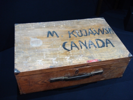 Colour photograph of a rectangular wooden suitcase with the words 'M KUJAWSK, CANADA' painted on the top of the case.