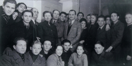Black-and-white photograph of a large group of about thirty youth, grouped in two rows and smiling at the camera. An older man in a suit stands in the middle of the group.