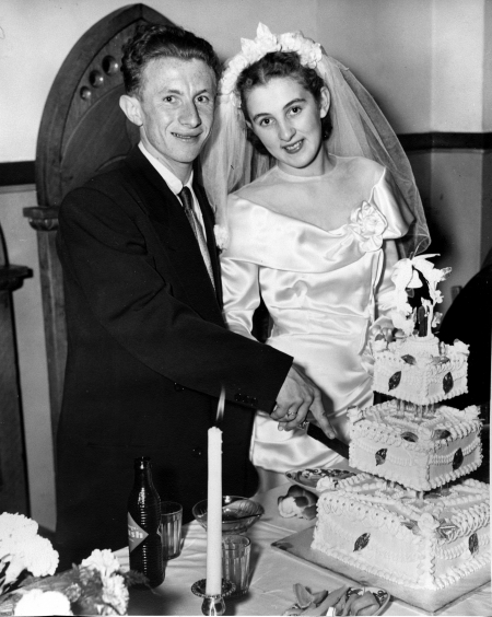 Black-and-white photograph of a man and woman standing together behind a table that holds a large, three-tiered cake. The couple, celebrating their wedding day, are cutting into the cake. They smile at the camera. The man wears a suit, and the woman wears a white silk gown with a veil.