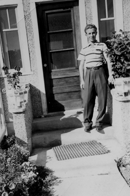 Black-and-white photograph of a young man standing outdoors, on the first step of an entrance to a house. He wears a short-sleeved striped shirt and trousers.