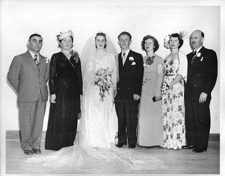 Black-and-white photograph of a group of seven people, standing in a line and smiling at the camera. The couple in the middle appears to be celebrating their wedding day, with the woman dressed in a long white gown, veil, and holding a bouquet of flowers. The men in the group wear suits, and the other three women wear dresses.